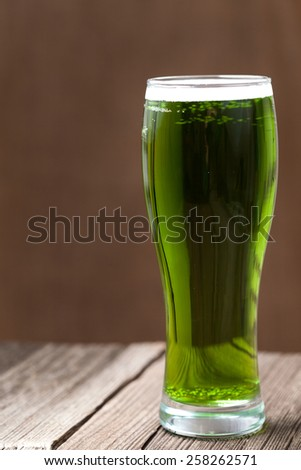 Green beer in glass with bubbles for st. patricks day on wooden background - stock photo