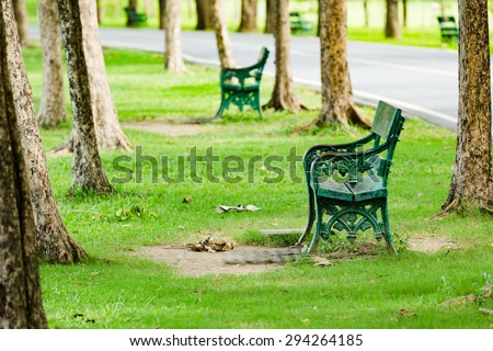 Green bench in a public park on a lovely summer day - stock photo