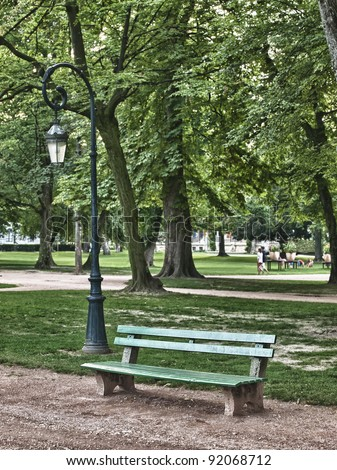 Green  bench in peaceful park in Annecy - stock photo