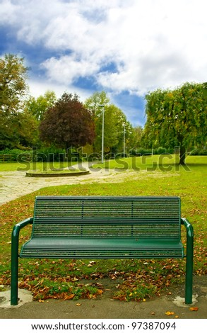 Green bench in the park - stock photo