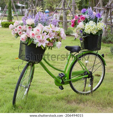 Green bicycle and flowers in park - stock photo