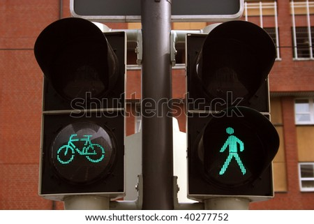 Green bicycle and pedestrian traffic lights, seen in Braunschweig, Germany - stock photo