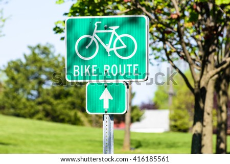 Green bike route sign on the parks