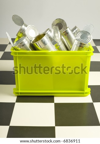 Green bin full up with tins standing on floor. Front iew - stock photo