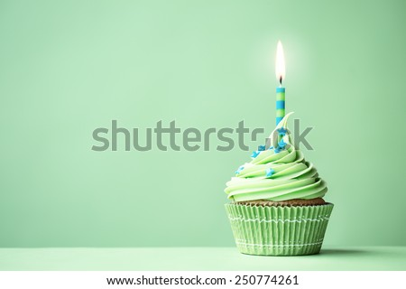 Green birthday cupcake with copy space to side - stock photo