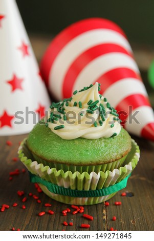 Green birthday cupcake with hats in background
