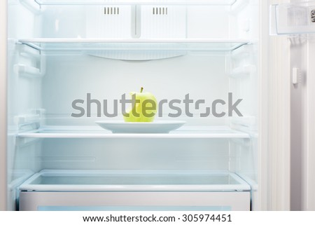 Green bitten apple on white plate in open empty refrigerator. Weight loss diet concept. - stock photo