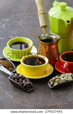 green, black coffee beans and different utensils for boiling coffee (grinder, kettle, cezve) - stock photo