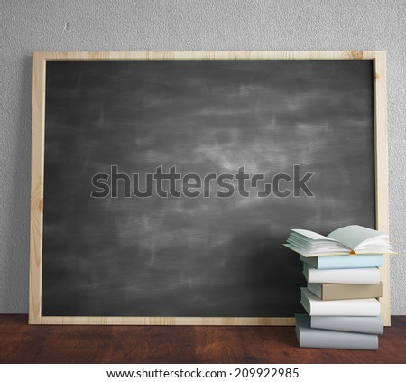 green blackboard and book standing on wooden floor - stock photo