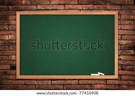 green blackboard on wall background. - stock photo
