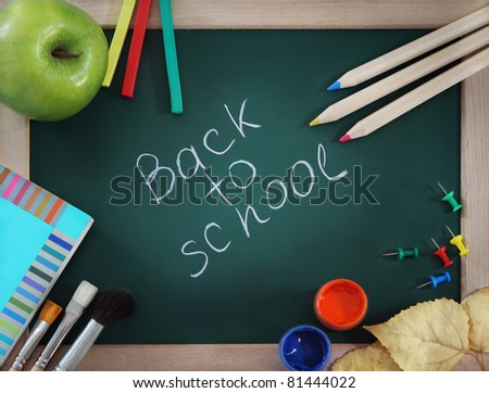 Green blackboard with brushes, book, apple and pencils - stock photo