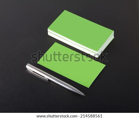 green blank business cards with pen on a black leather background - stock photo