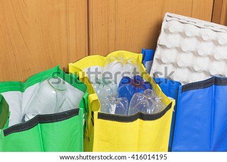 Green, blue and yellow bags for sorting household waste are filled with waste - paper, plastic and glass. - stock photo