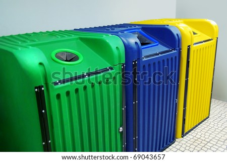 Green blue and yellow recycling materials containers in a alley - stock photo