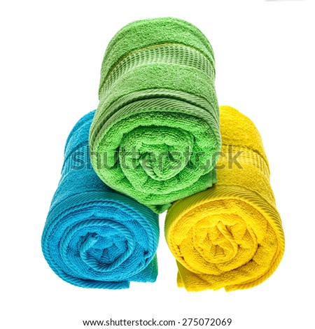 Green, blue and yellow towels pile isolated on white background. - stock photo