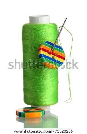 Green bobbin with needle and buttons isolated on white - stock photo