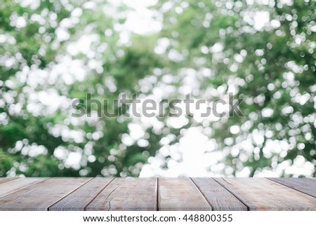 Green bokeh and sunlight and wood floor. Beauty natural background - can be used for montage or display your products - stock photo