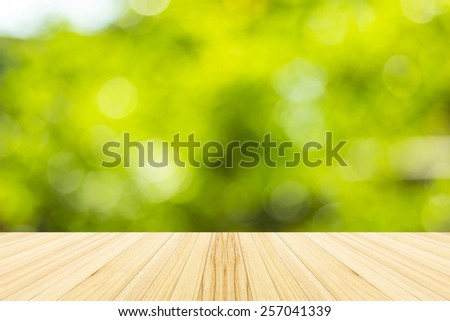 Green bokeh and sunlight with wood terrace. - stock photo