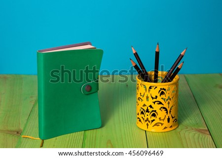 Green Book, notebook on an blue background on a green wooden table, yellow stand with pencils, no labels, blank spine. Back to school