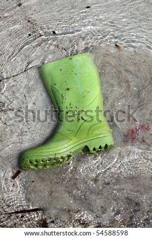 green boots trash on beach shore pollution human waste concept - stock photo