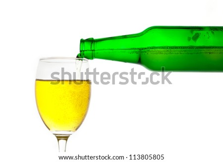 Green bottle of beer pouring into glass on white background - stock photo