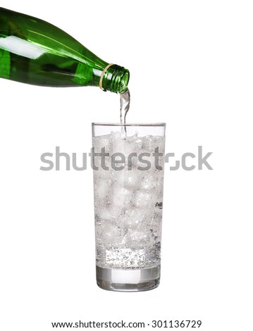 green bottle pouring water in glass of cold mineral carbonated water with ice cubes Isolated on white background - stock photo