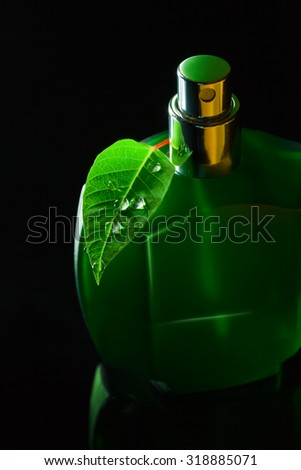 Green bottle with natural perfume on a black background