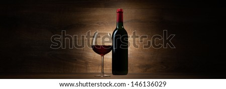 green bottle with red wine and glass on a wood panorama background - stock photo