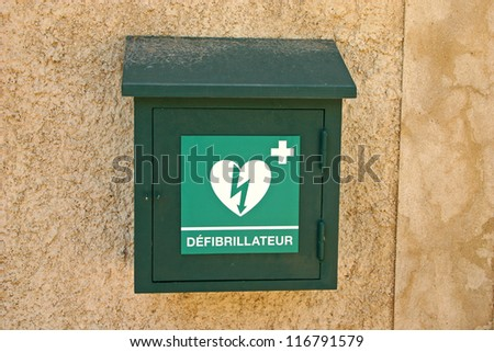 Green box with defibrillator (defibbrillateur) in France - stock photo