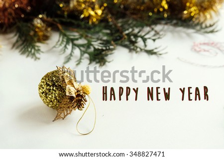 green branches and amazing christmas golden ball on white background, happy new year text
