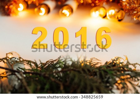 green branches and amazing christmas golden vintage garland lights on white background, merry christmas text