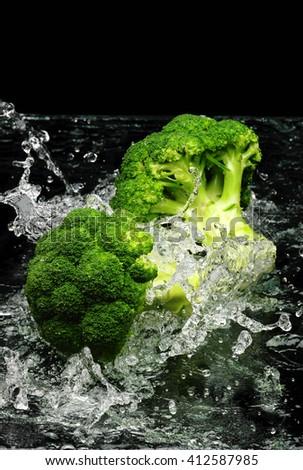 Green broccoli falling in water on black  - stock photo