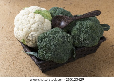 Green broccoli in a wicker basket on a wooden background - stock photo