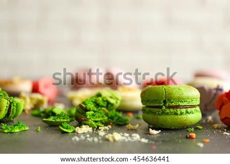 Green broken tasty macaroons on gray table - stock photo