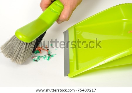 Green brush and dustpan with some garbage on white background