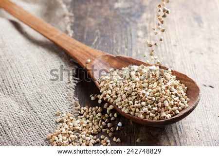 green buckwheat spilling in a wooden spoon on a background of burlap and dark old wooden table in rustic style