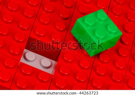 Green building block in a field of red ones - stock photo