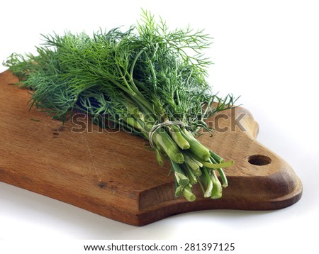 green bunch of dill on a small cutting board - stock photo
