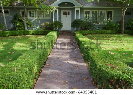 Green bush lined home brick entrance to a white doored gray home - stock photo