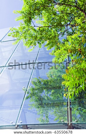 Green business and glass office building with reflections