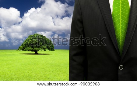 green business concept.Businessman with leaf tie and old tree background - stock photo