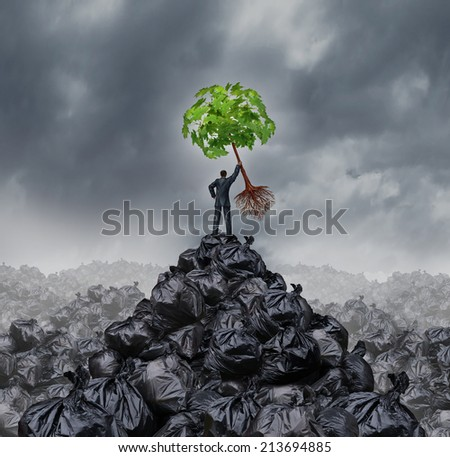 Green businessman concept as a man on top of a mountain heap of garbage holding up a green leaf tree with roots as an environment or conservation icon for waste management or a new healthy beginning. - stock photo