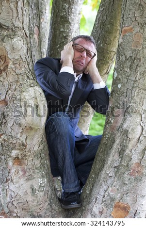 green businessman - depressed businessman in pain seeking for peace and protection within a tree from noise and corporate problems,avoiding company nightmare or city stress - stock photo