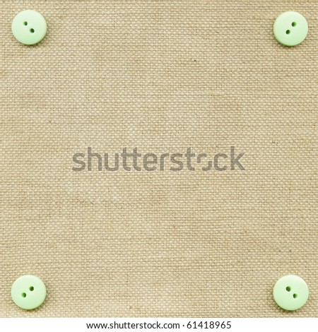 Green buttons on the beige fabric - stock photo