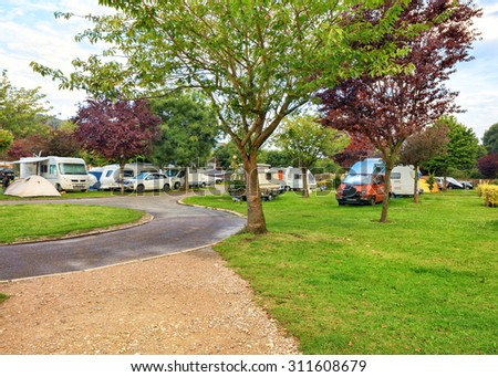 Green camping loan in Europe with vehicles and tents  - stock photo