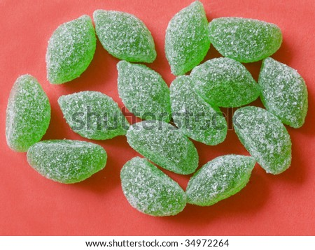 green candies on red background - stock photo