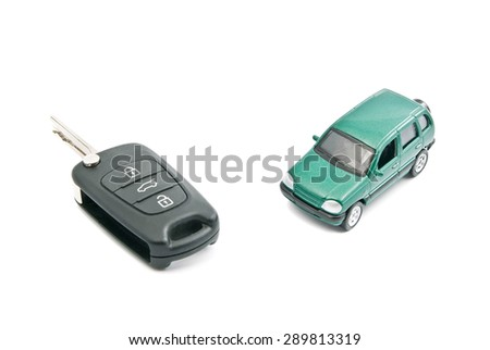 Green car and black car keys on white