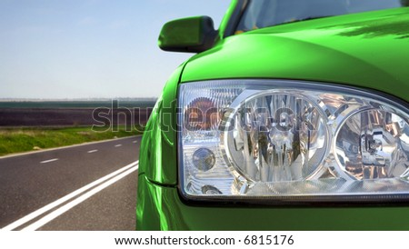 Green car on the road - stock photo