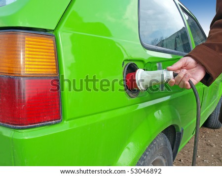 Green car using electricity as the fuel - stock photo