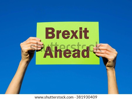 Green card placard with the concept of Brexit Ahead against a clear blue sky background - stock photo